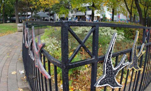 Mosaic birds mounted on wrought iron fence
