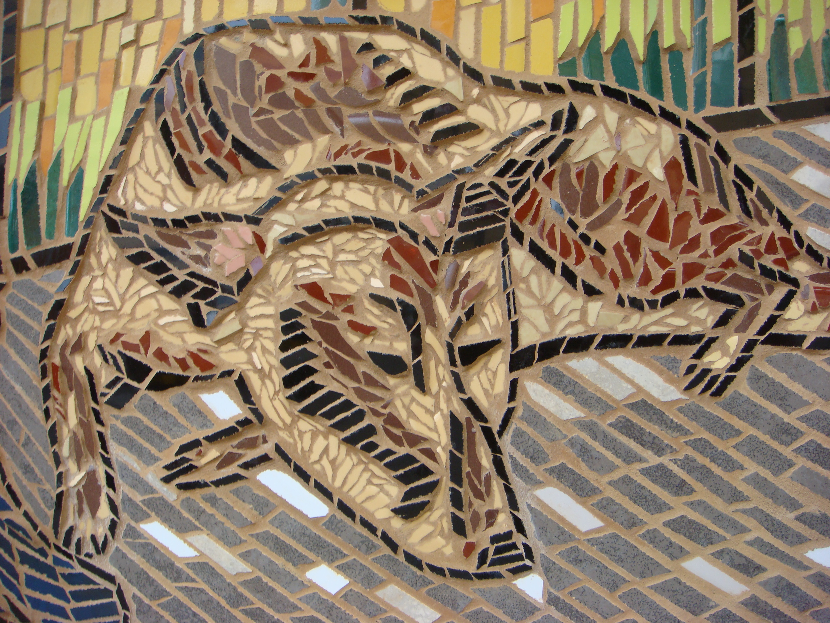 [Image description: A photograph showing the close-up of a tiled mosaic depicting a large dog coloured in reds and browns lying down on its stomach, against a green backdrop]