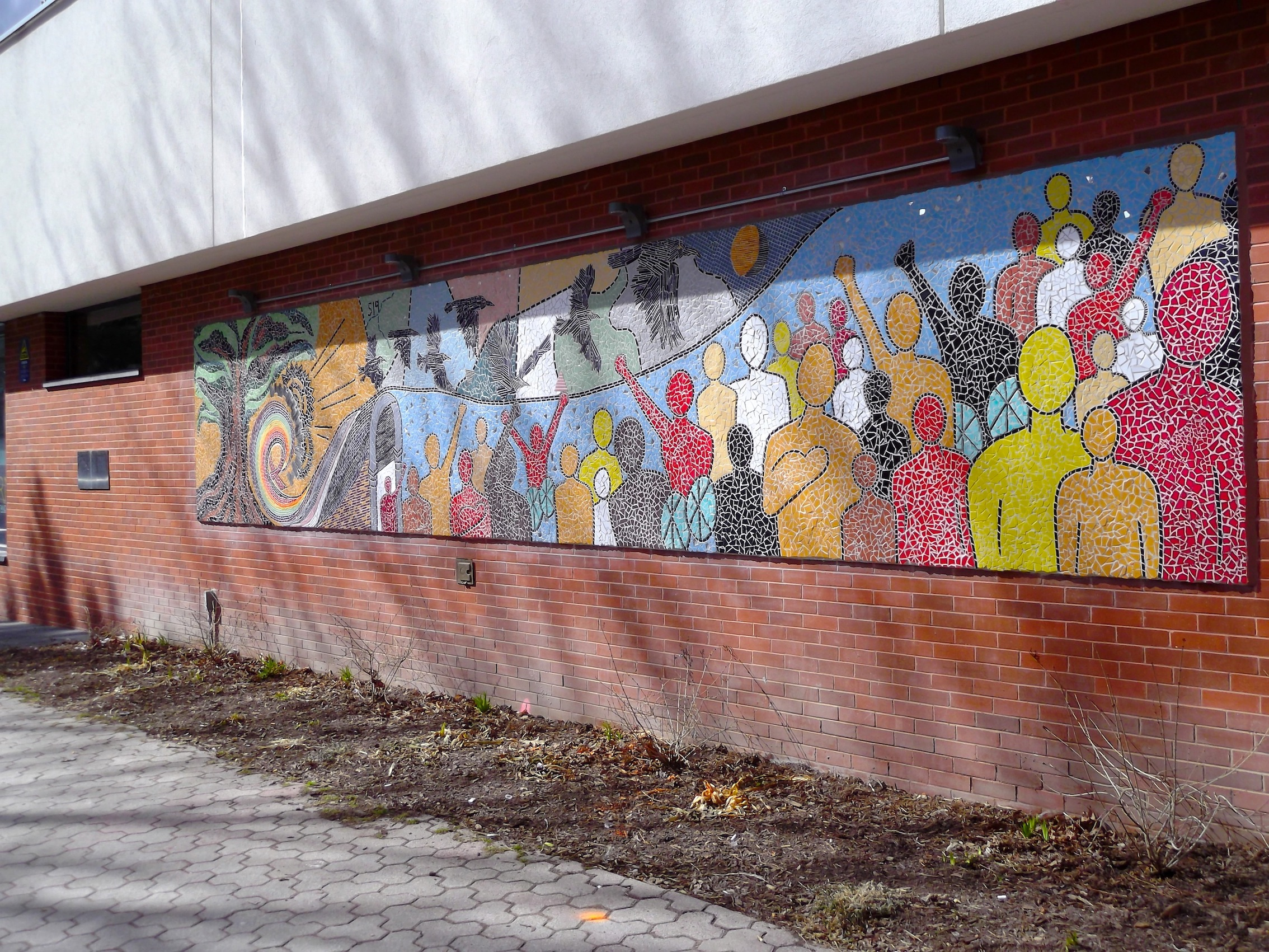 [Image description: A sideways photograph of the full-length rectangular mural running on a brick wall. The mural shows people of all colours and abilities standing together while black birds fly overhead in a colourful sky with a sun, a spiral rainbow, and a red AIDS ribbon all included in the design]