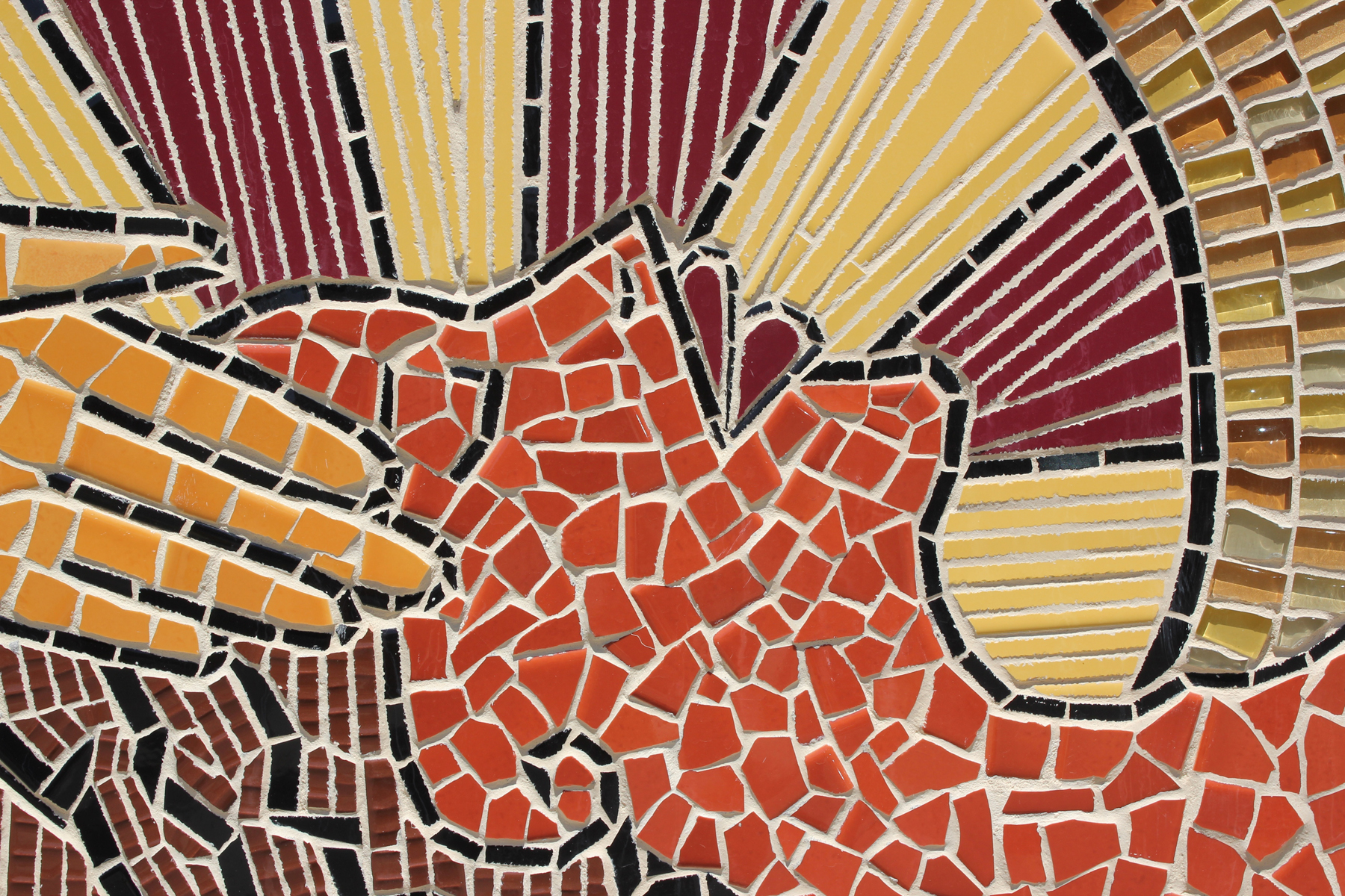 [Image description: A close-up of a mural in earthy browns, reds, and oranges, depicting a woman against a haloed background, with hands massaging her head and her eyes are closed in bliss]