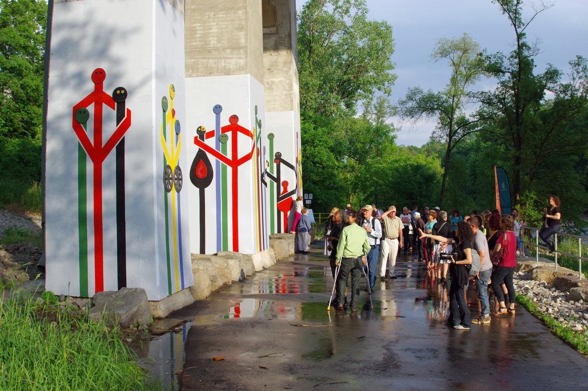 [Image description: A photograph of a path with three large concrete pillars painted white and depictions of stick figures coloured black, blue, green, yellow, and red hugging or standing beside each other. Spectators stand in front of the pillars looking at the art]