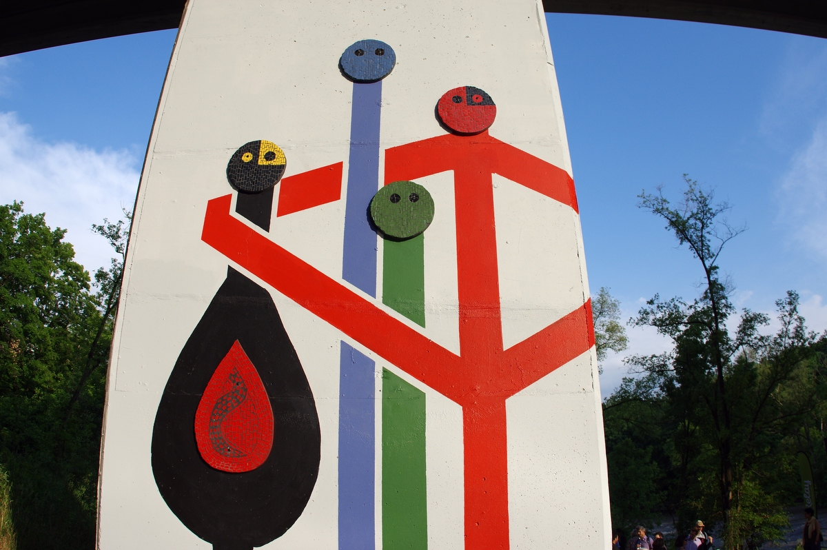 [Image description: A photograph of a tall square concrete pillar painted white. A cartoon stick painting of four stick figures with circle heads in black, blue, green, and red, standing beside and hugging each other]