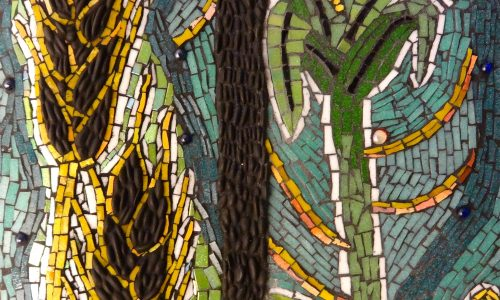 [Image description: A photograph of a close up of a mural using tiny tiles. The mural shows stalks of what and corn]