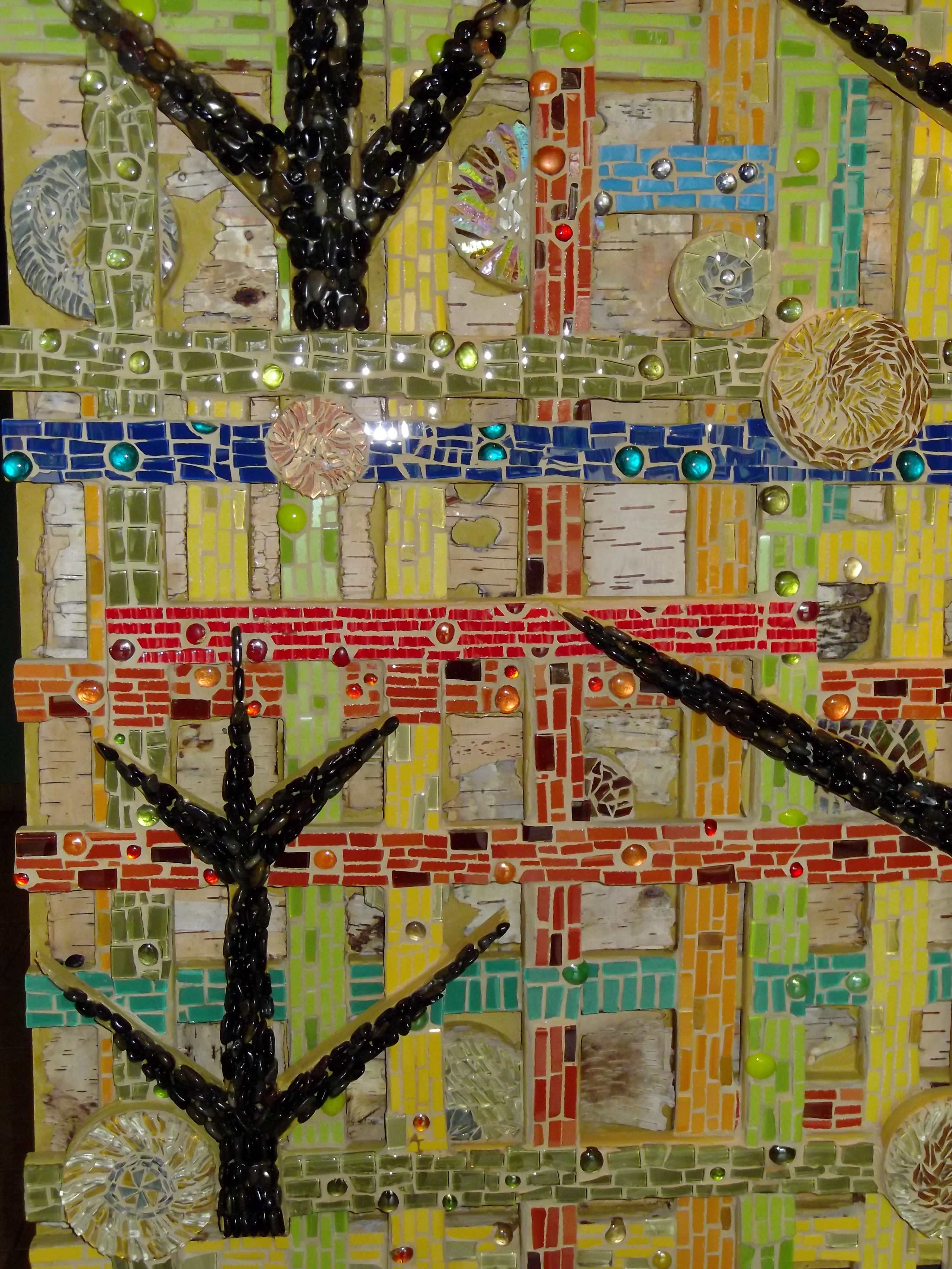 [Image description: A photograph of a mixed media abstract piece of art made of mosaic tiles and other 3-D pieces]