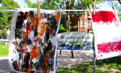 "Image description: a photograph of a sunny summer day. In the foreground hang finger paintings on sheets of paper on a clothes line. In the background is a park sign that reads ""Winchester Park""."