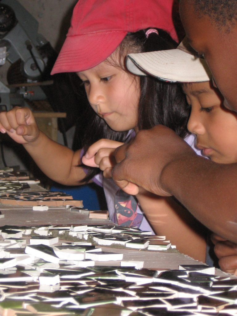 [Image description: A close up of the faces of three young children busily sorting through various mosaic tiles laid out on the table in front of them]