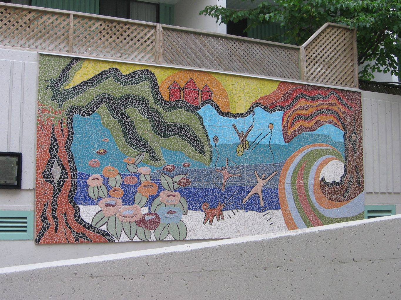 [Image description: A photograph of a full-length rectangular mural on a wall fence, depicting a tropical beach with sand, sun, waves, and a dog barking at people playing a game on the sand, including a person in a wheelchair]