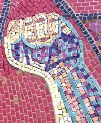 [Image description: A photograph of the close up of the mural, showing the colourful tiles used to create the fist]