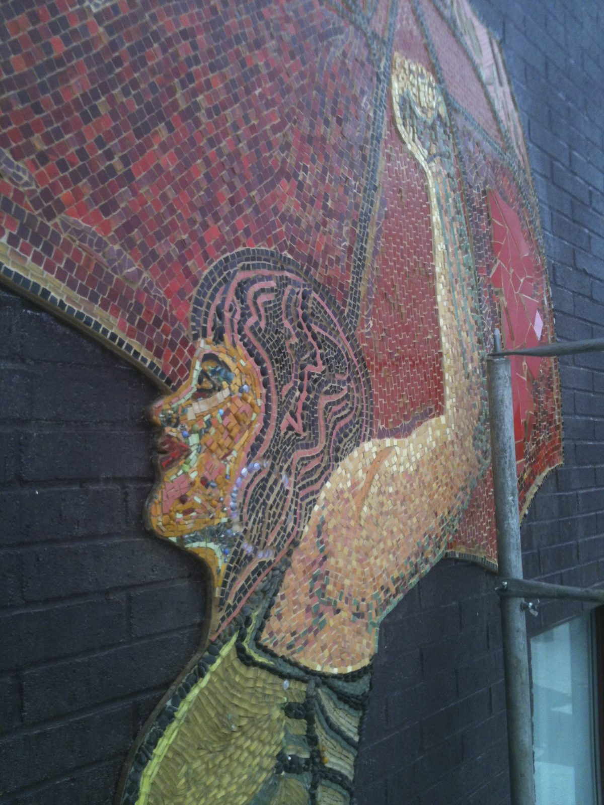 [Image description: A photograph of the mural of the woman from a different angle, showing the multicoloured tiling detail and her smiling face]