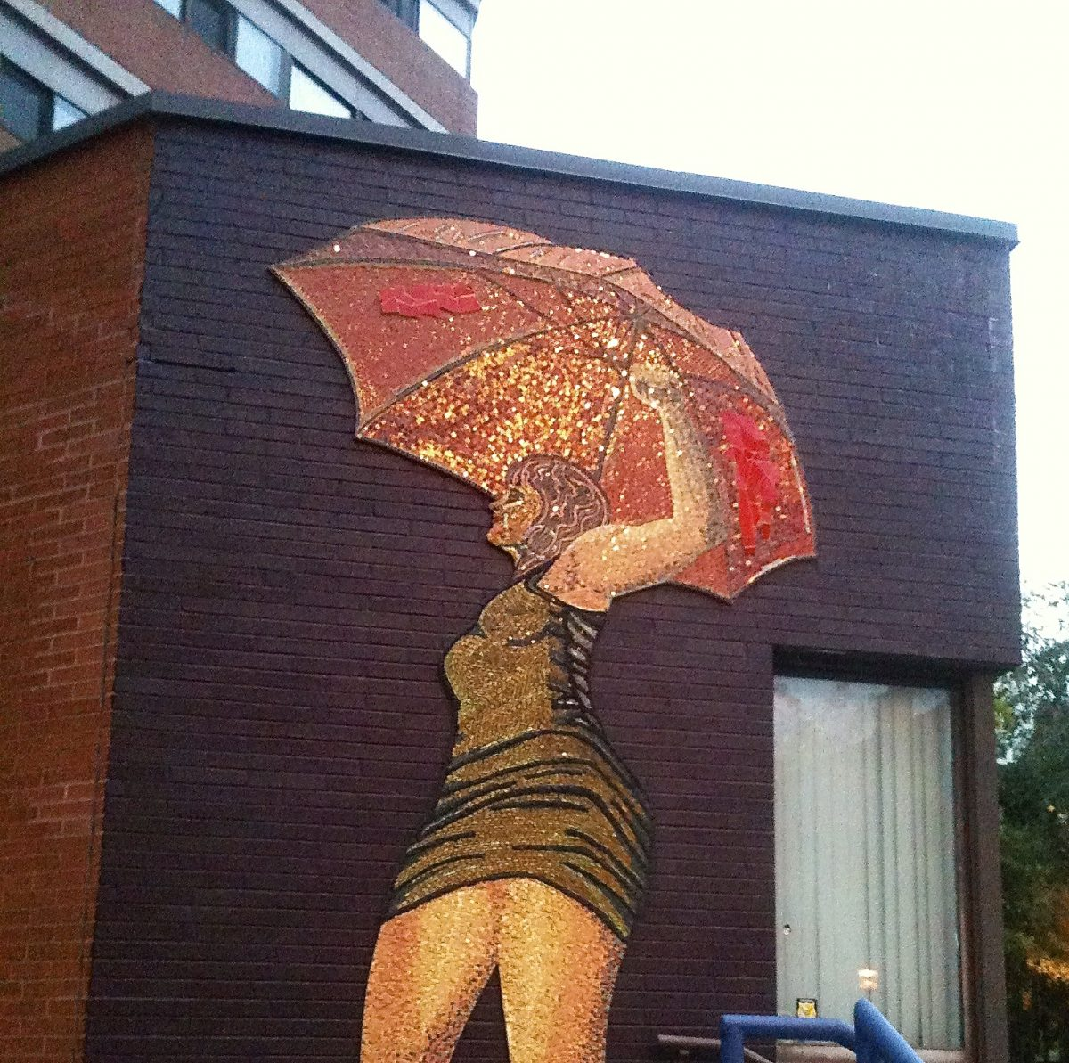 [Image description: A photograph of a mural on a brick wall. The mural shows a woman in a short, tight black dress holding an umbrella, and has one fist raised high]