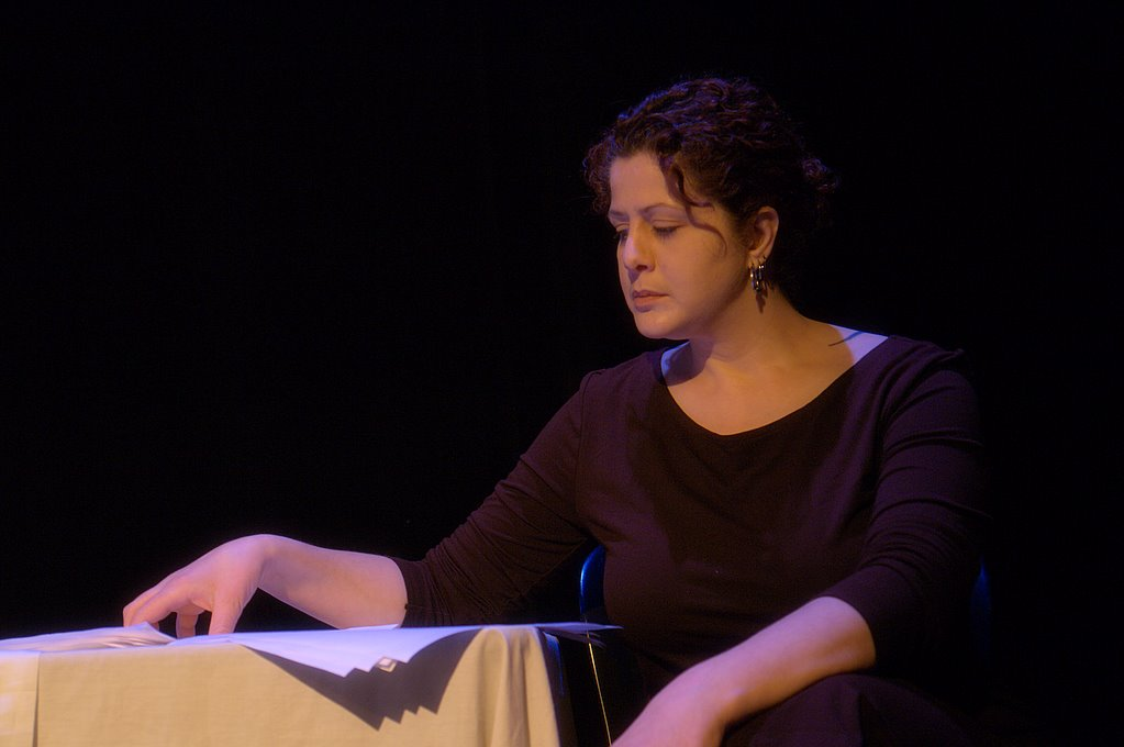 [Image description: A photograph of Anna, a light-skinned woman with curly dark hair. She is sitting on a black stage at a table, wearing dark clothing and looking down at papers]