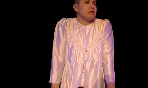 [Image description: A photograph of a stage, with a person with close cropped hair in a shiny white robe. The person is standing behind a table and looking out with a distressed expression]