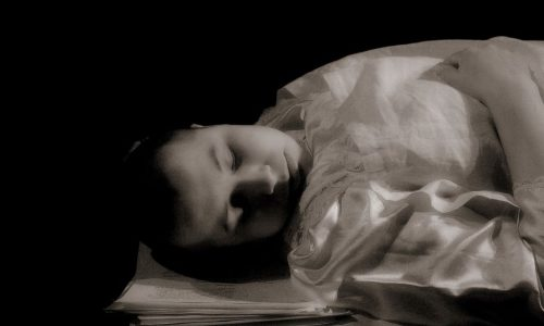 [Image description: A black and white photograph of a close up of a person with close cropped hair and a baby face lying on a flat surface asleep. The setting appears to be on a theatre stage with a black background]