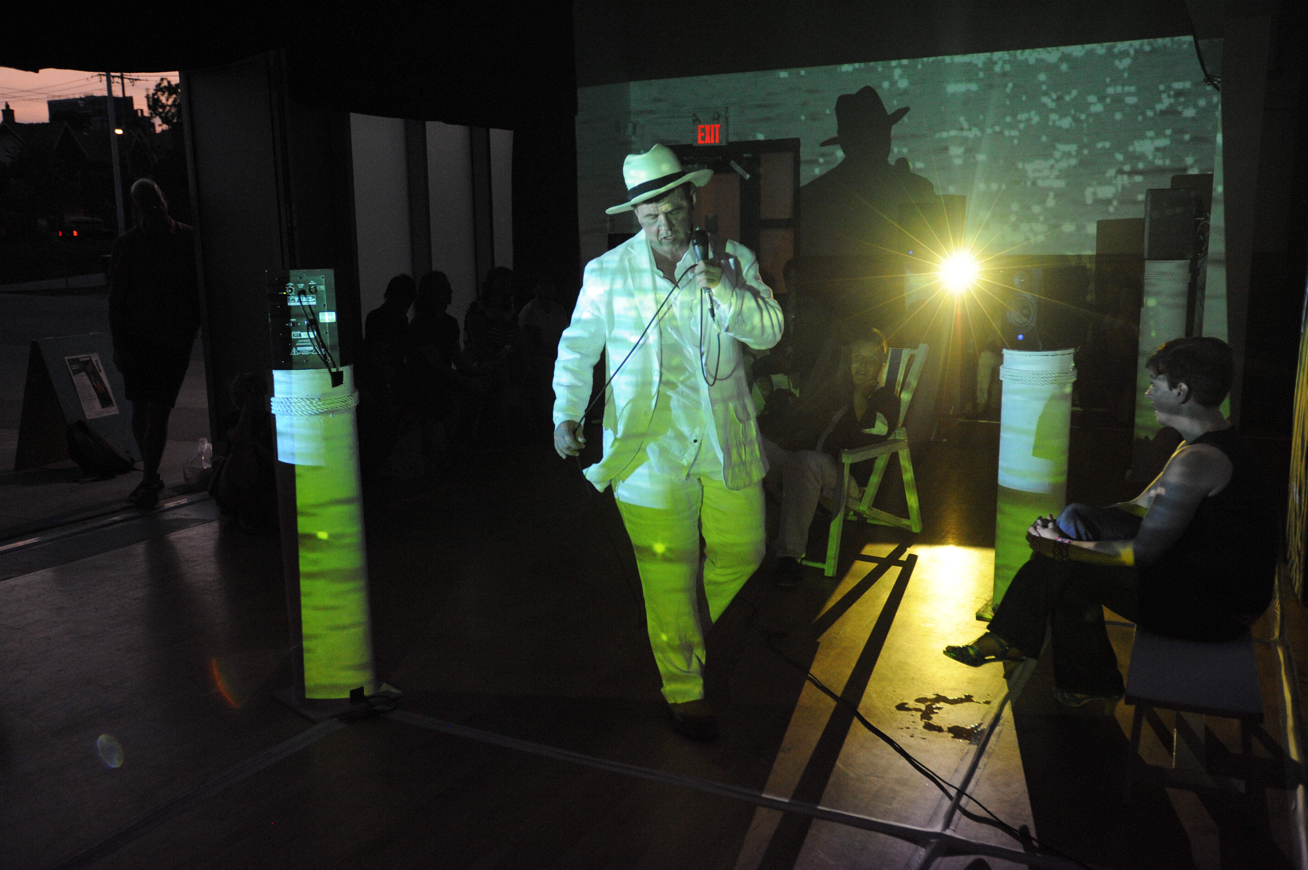[Image description: A photograph of a man on the set of a play, in dim lighting, lit by a green light. The man is wearing an all-white suit and white fedora]