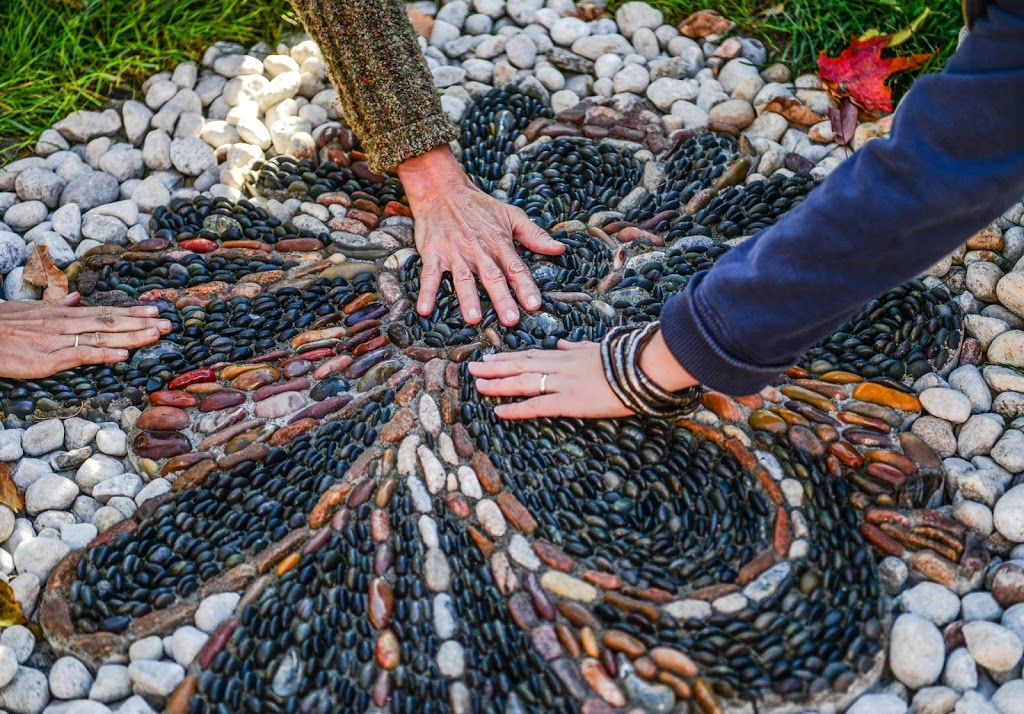 Three hands touch a small pebble mosaic monument