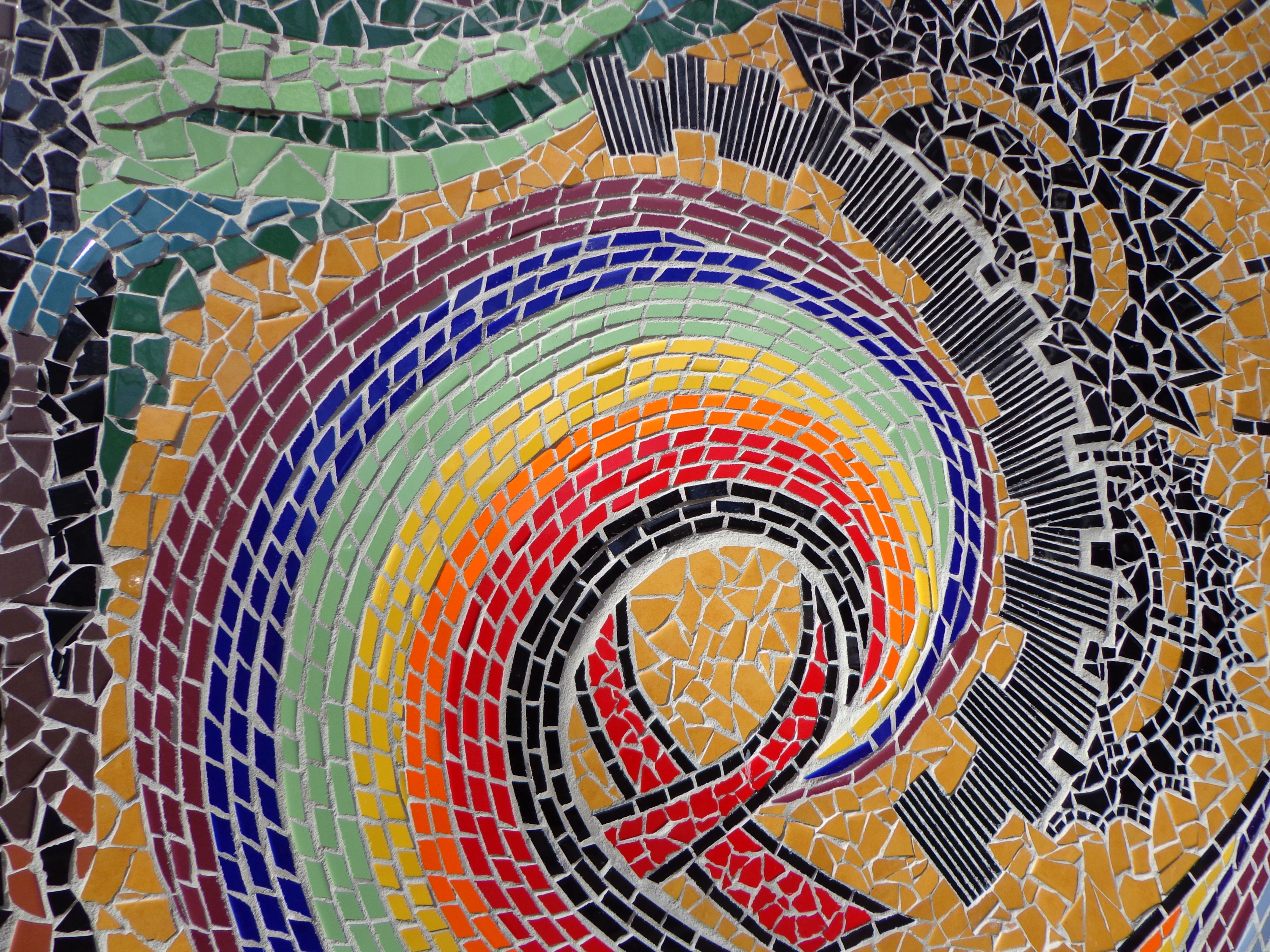[Image description: A photograph close up of a section of the mural showing the red AIDS ribbon and the spiral rainbow emerging out of it]