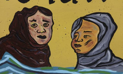 [Image description: A close up of the painting on the yellow wall, showing two persons with either brown and grey hair or head coverings, emerging out of the waves]