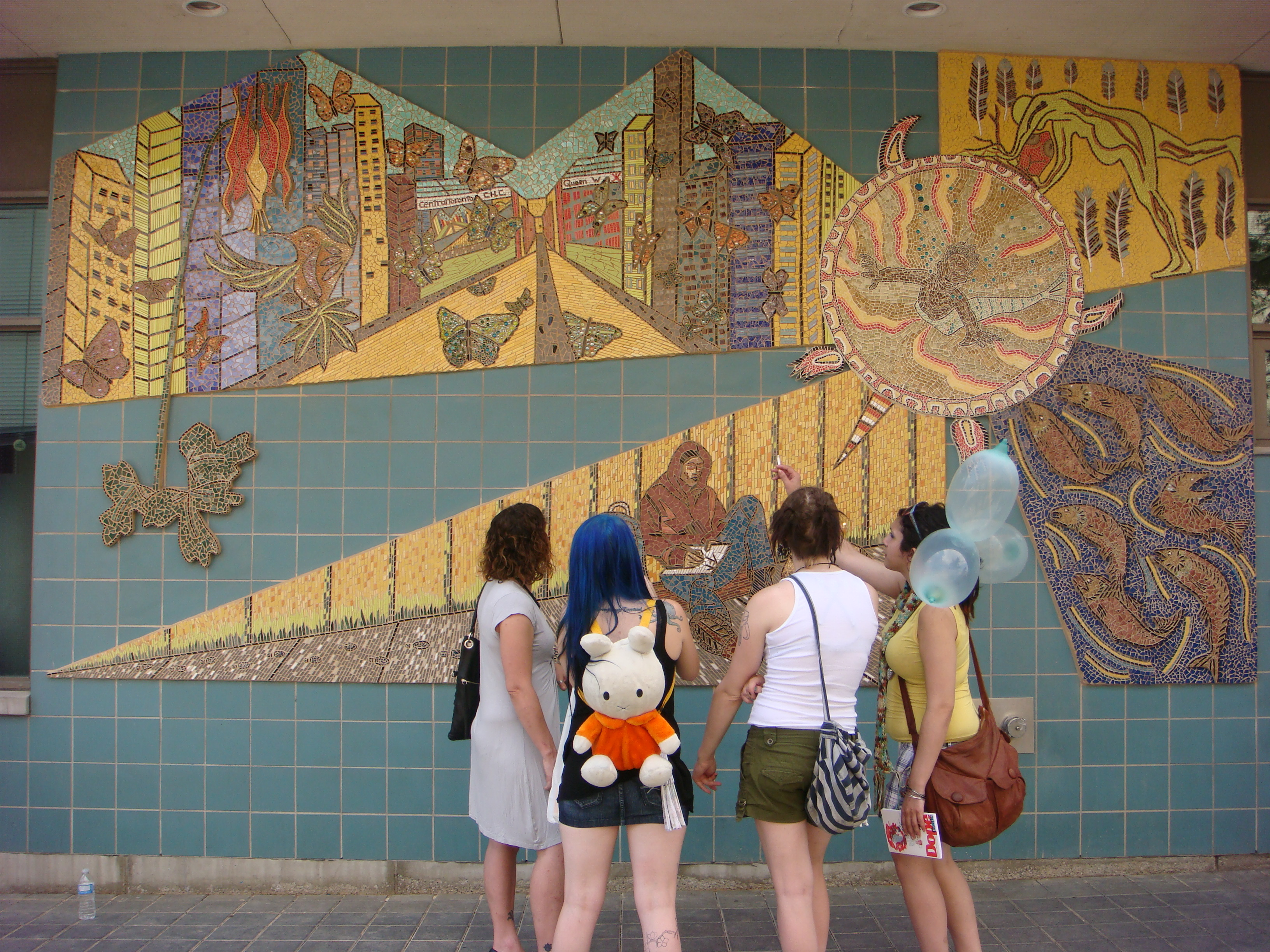 [Image description: A photograph of four people looking at a mural on a wall. The mural is coloured in muted earthy tones and depicts a downtown cityscape with birds and butterflies flying, as well as a person reading a book, a human figure pushing a turtle representing Turtle Island, and many fish crowded together]