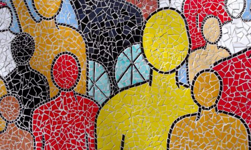 [Image description: A close up photograph of a mosaic, showing figures of people in all colours and physical abilities]