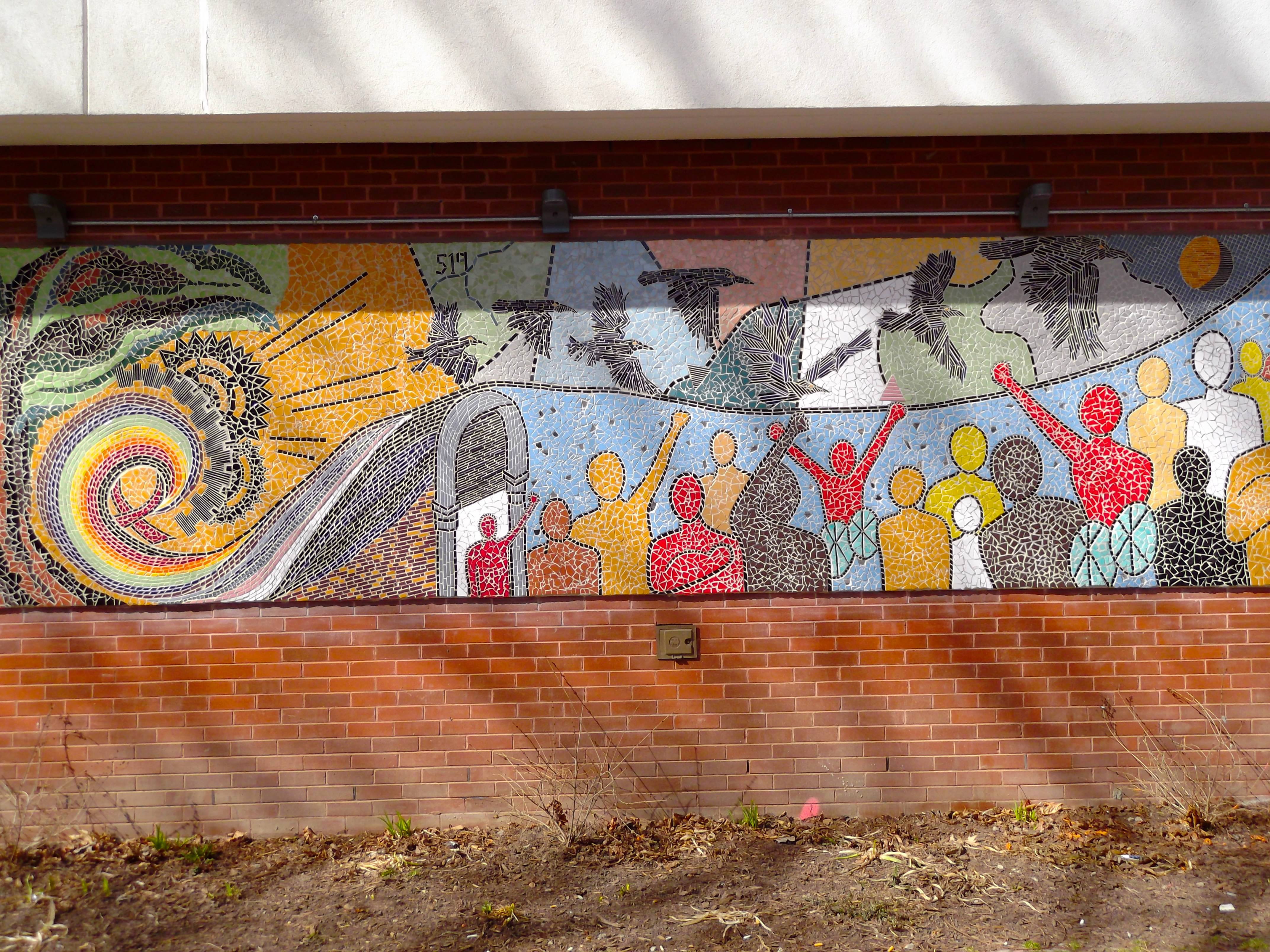 [Image description: A photograph of the full-length rectangular mural running on a brick wall. The mural shows people of all colours and abilities standing together while black birds fly overhead in a colourful sky with a sun, a spiral rainbow, and a red AIDS ribbon all included in the design]