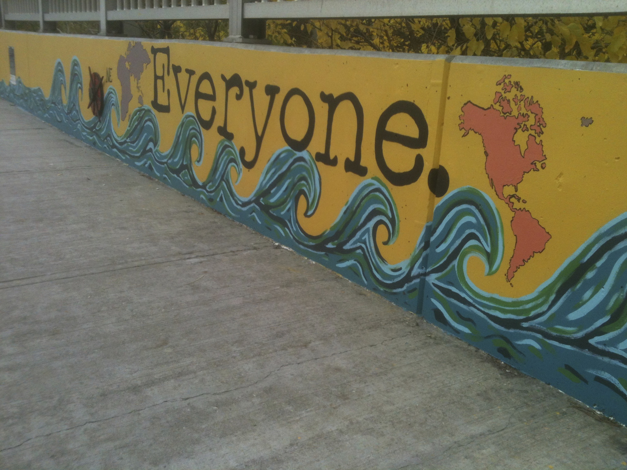 "[Image description: A photograph of a low yellow wall. There are cartoon-like curvy blue waves running along the bottom and outlines of the world map. In the centre in big black letters is the word ""Everyone.""]"