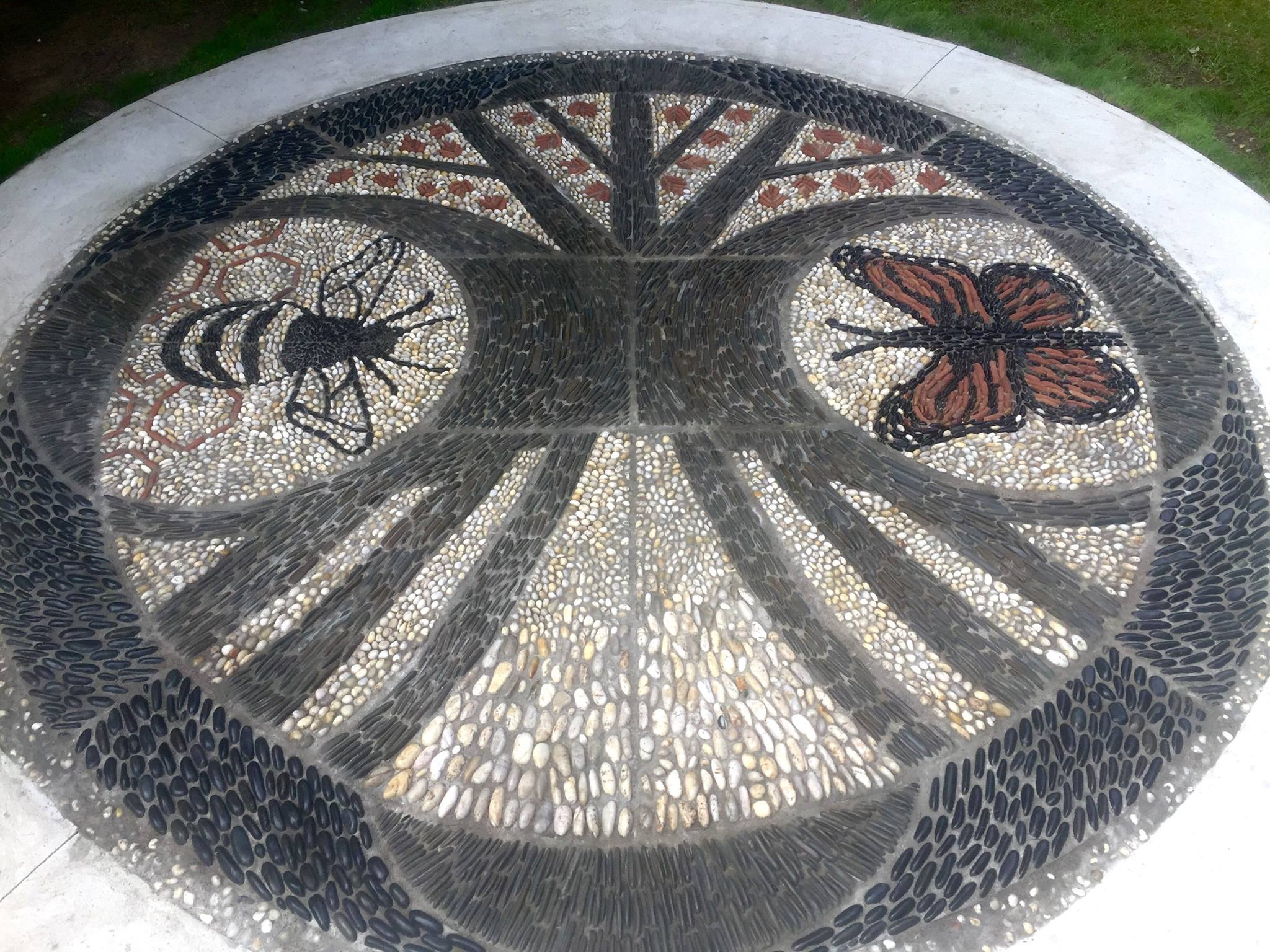 This is a close up image of a circular pebble mosaic. The image on the mosaic is of a tree with leaves and a trunk and roots, and a large bee on one side and a large butterfly on the other side. The colours of the mosaic are grey, yellowy white, red and black.