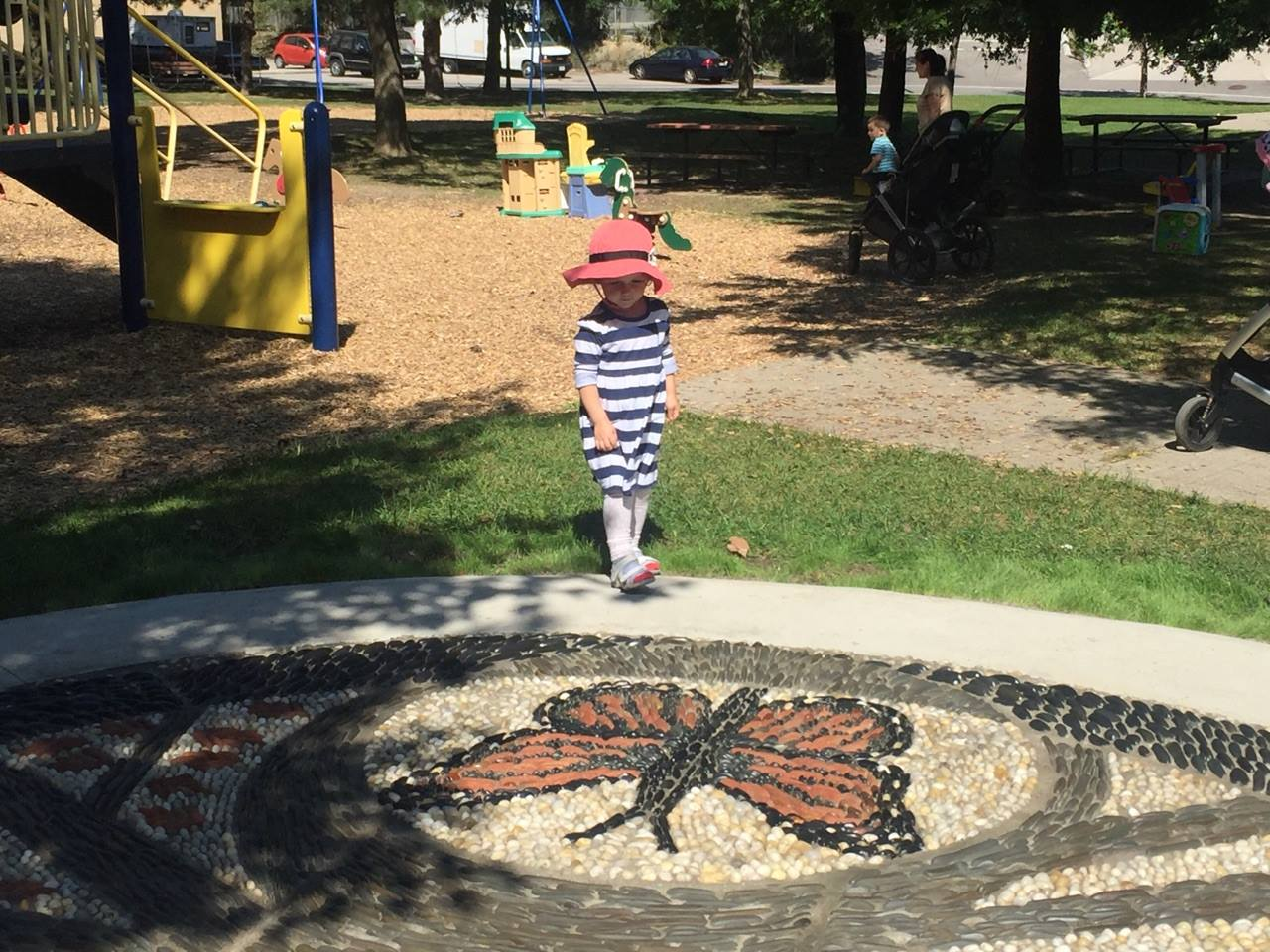 A child stands at the edge of a playground looking down at the edge of the pebble mosaic. The child is wearing a red hat and looks down at a large butterfly made of pebbles.