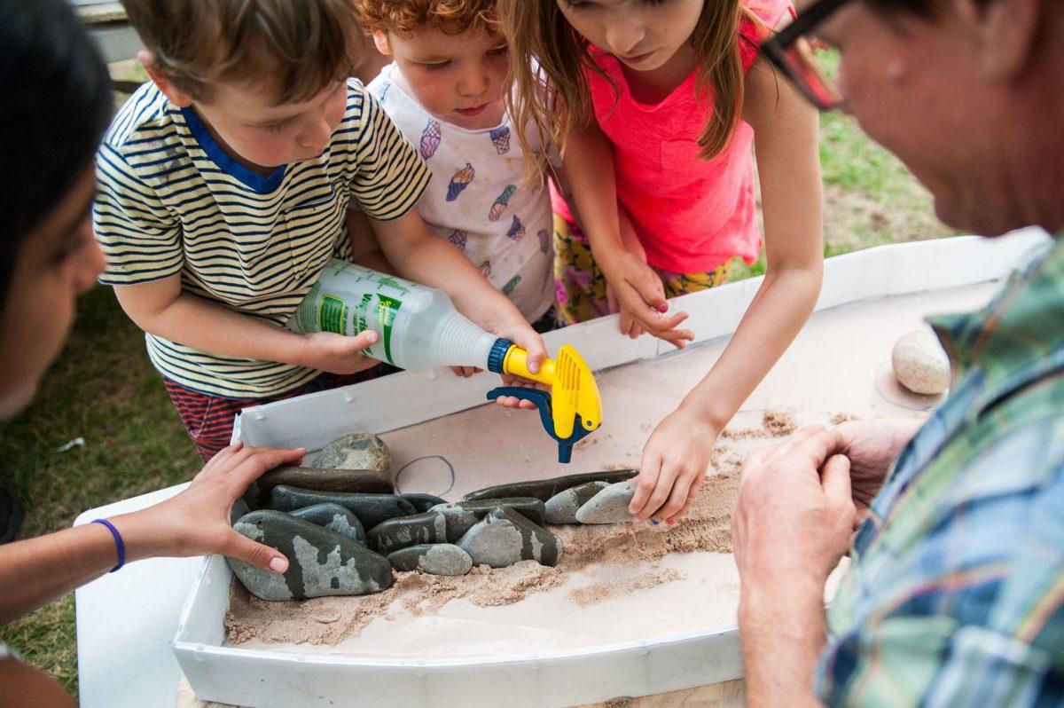 Children help assemble pebble mosaic
