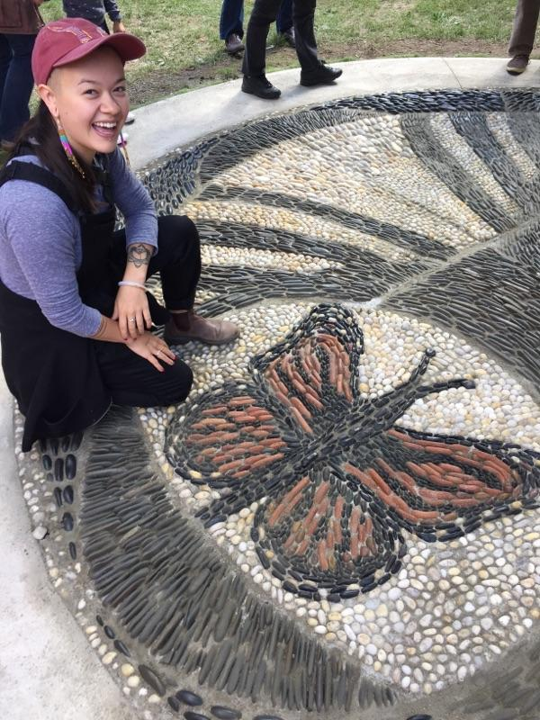 This is a close up image of one of the artists kneeling by a details of a circular pebble mosaic. The image on the mosaic is of a butterfly with red and black wings.