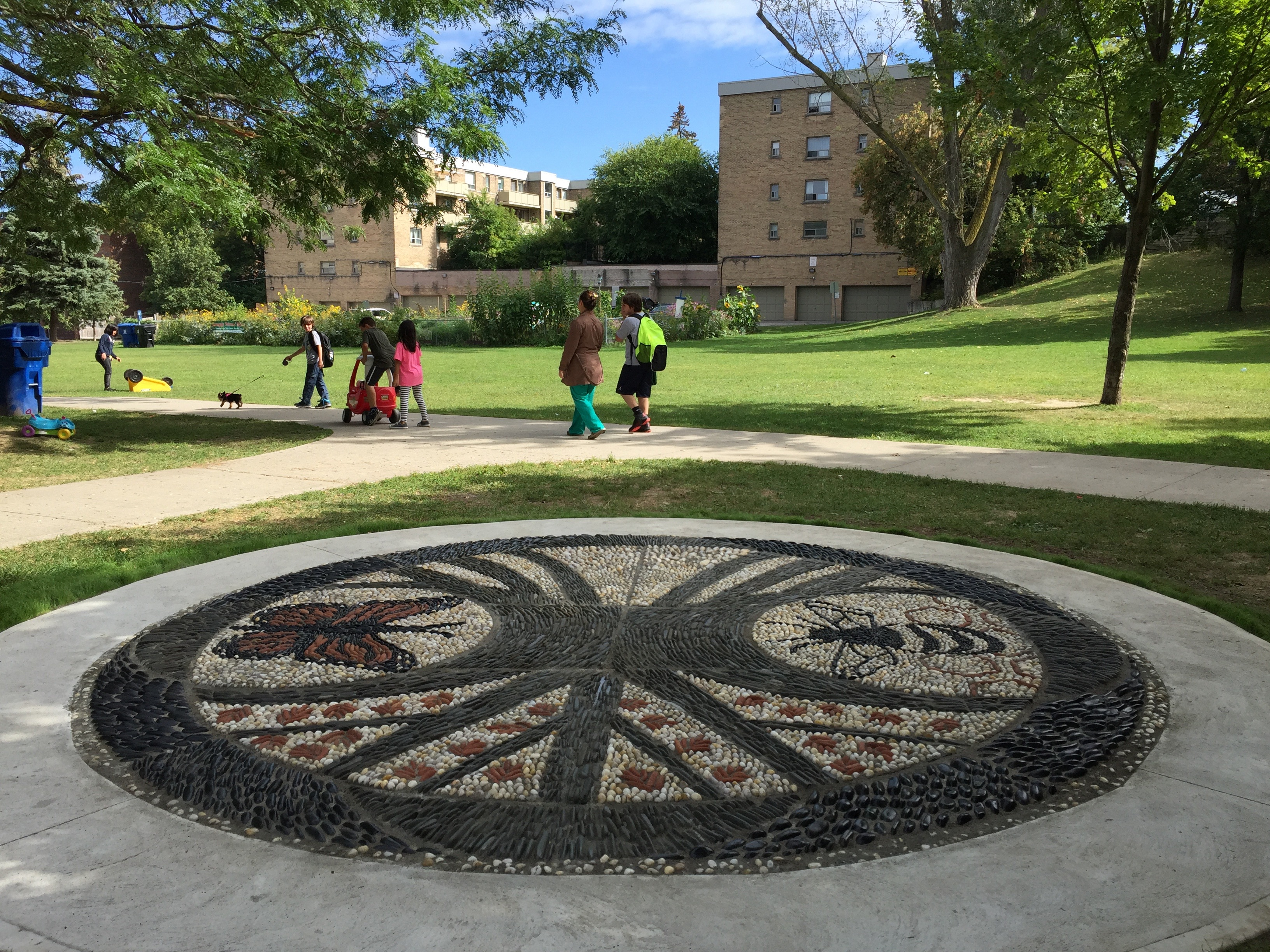 This is an image of a circular pebble mosaic on the ground of a park. In the foreground the image shows a circular pebble mosaic and in the background there is grass and some apartment buildings.