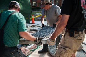 Katie, Doug and Tristan carry a pebble mosaic slab.