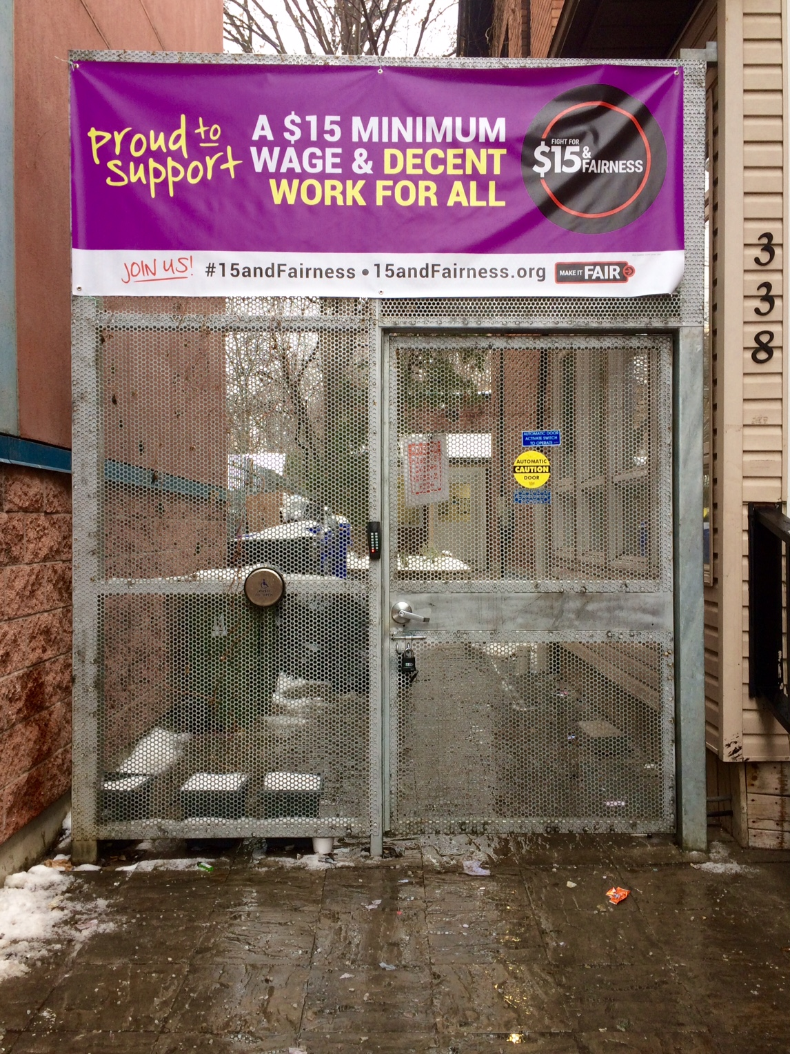 """The image shows a metal gate between two buildings. At the top of the gate is a purple banner that reads """"Proud to support A $15 minimum wage and decent work for all"""""""