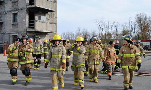 A group of women firefighters dressed in full firefighting gear walk down the road together.