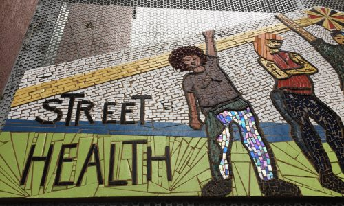 A detail of the new mosaic artwork on the gate at Street Health. The image is of the left side of the art, showing the words Street Health and two figures. The work is created of porcelain and glass tiles.