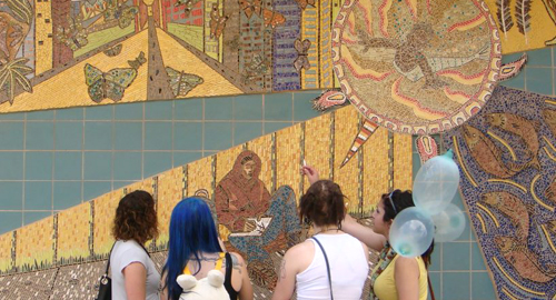 Young women look at mosaic at the Parkdale Queen West Community Health Centre