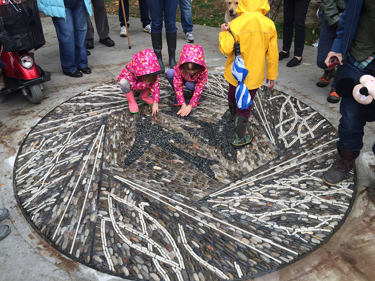 Children squat and rub their hands over the pebbles in the ground mosaic.