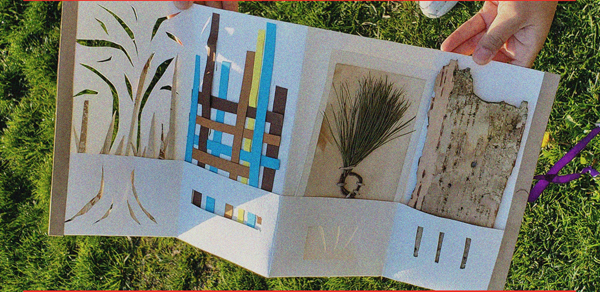 A white paper accordion book is laying on top of a sunny grass patch. The book has four panels, each side decorated with handmade cuttings and paper weavings. There are two foraged items inserted into two of the panels.