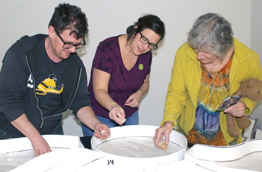 Tristan Whiston, Brigitte Lebel, and Roberta Della-Pica work on pebble mosaic