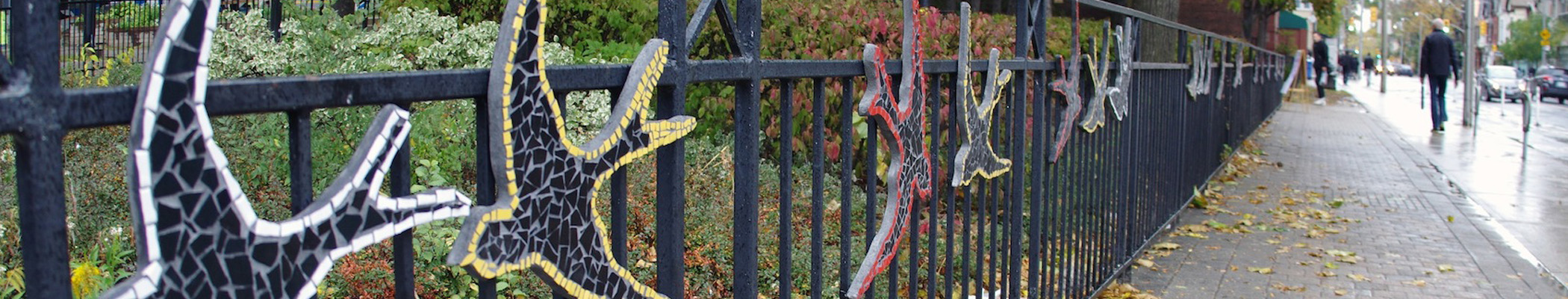Tiled mosaic birds line against a wrought iron fence in Cabbagetown
