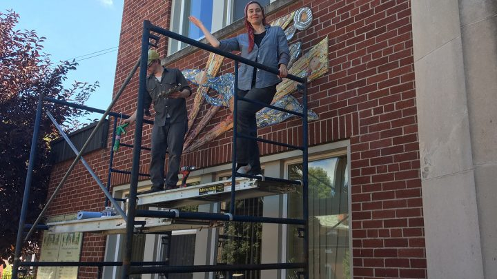 Megan Spencer mounting Pembroke youth mural
