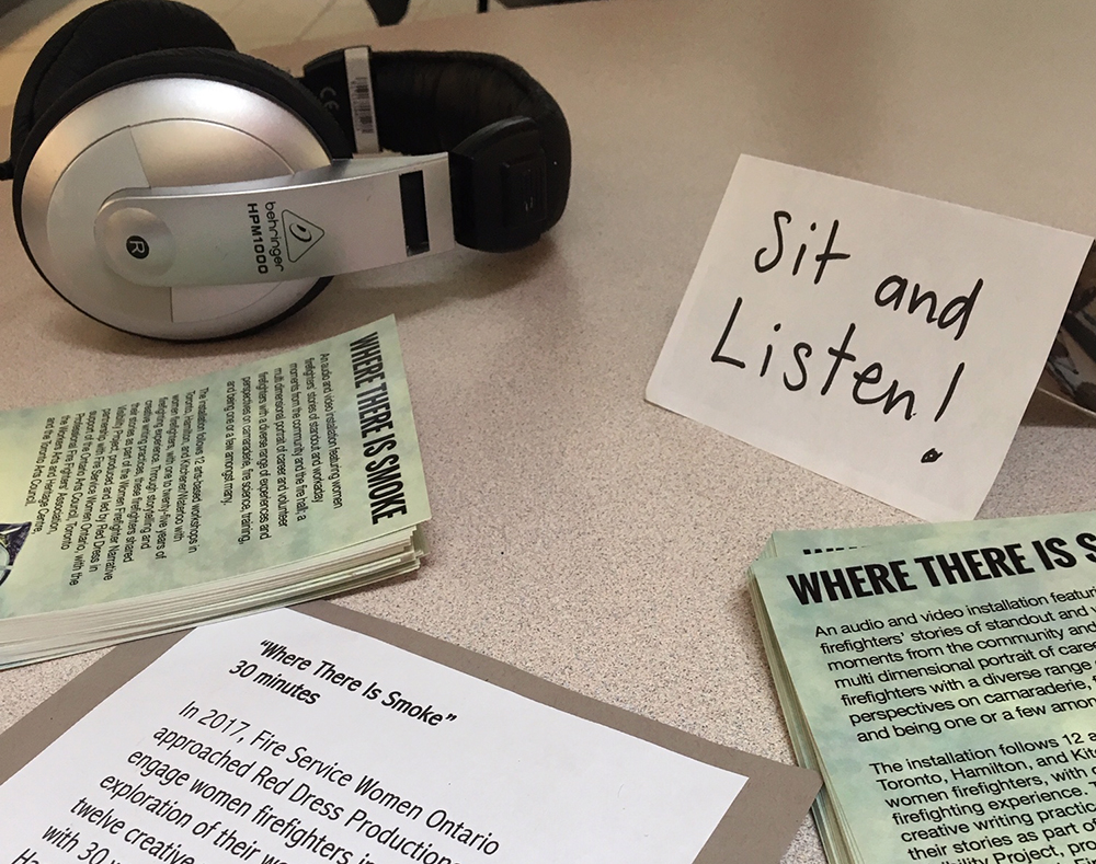 A headphone and flyers are displayed on a table with a sign that encourages attendees to sit and listen