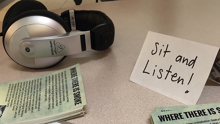 Headphone, flyers and sit and listen sign displayed on table