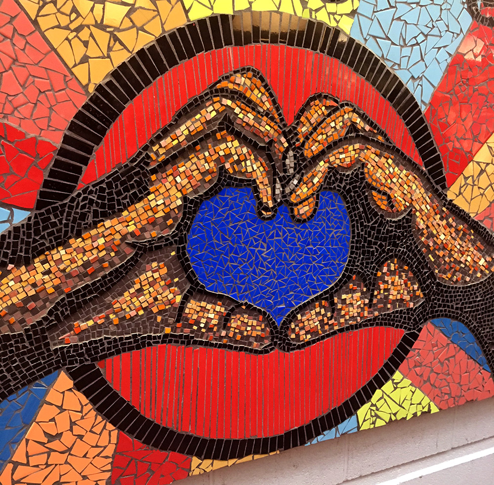 Hands form a heart in a close up of the Project Love mural