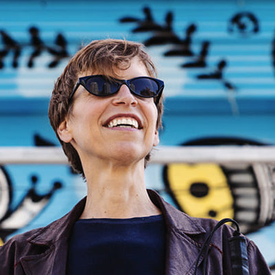 A photograph of Alex Bulmer. Alex is a white woman with short light brown hair. She wears black cat-eye sunglasses, and a burgundy leather jacket over a navy blue shirt. She stands in front of a blue and yellow mural and smiles widely.