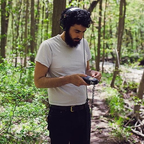 Anthony, a bearded man with dark curly hair, stands on a forest hiking trail, wearing headphones and looking at a portable sound recorder that he's holding in his hands. He is wearing a white t-shirt and black shorts.