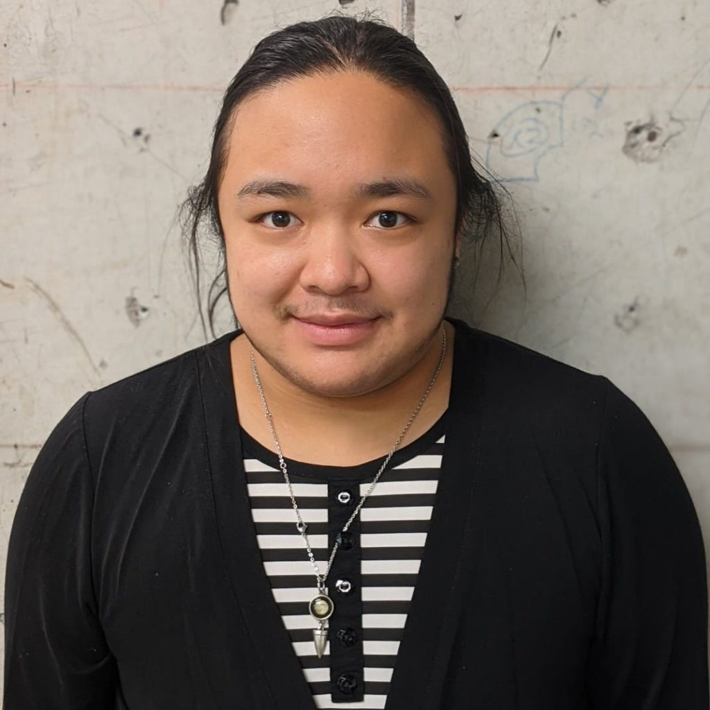 A closeup photo of Cam, a person of mixed Asian descent, standing in front of a textured concrete wall. They are wearing a black v-neck cardigan over a black and white striped button-down shirt. Their hair is black and pulled back into a ponytail with a few loose whisps at the sides of their face. They wear a silver chain with small pendants on it and smile slightly, looking directly at the camera.