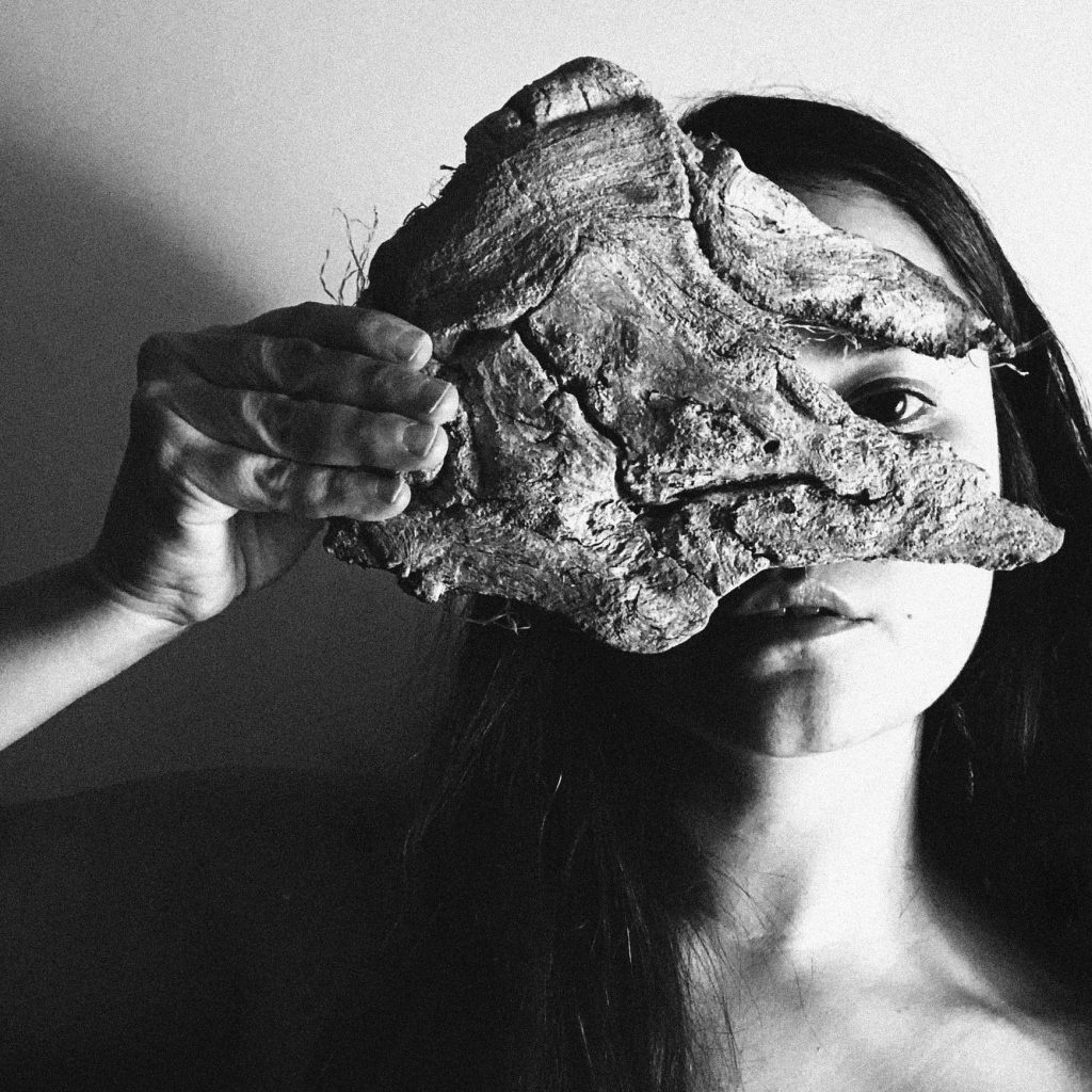 A black and white photograph of Cristal Buemi. Cristal has long dark hair and dark eyes. She holds a piece of tree bark in front of her face, as if it were a mask. Through a break in the bark we can see her left eye and the lower part of her face.