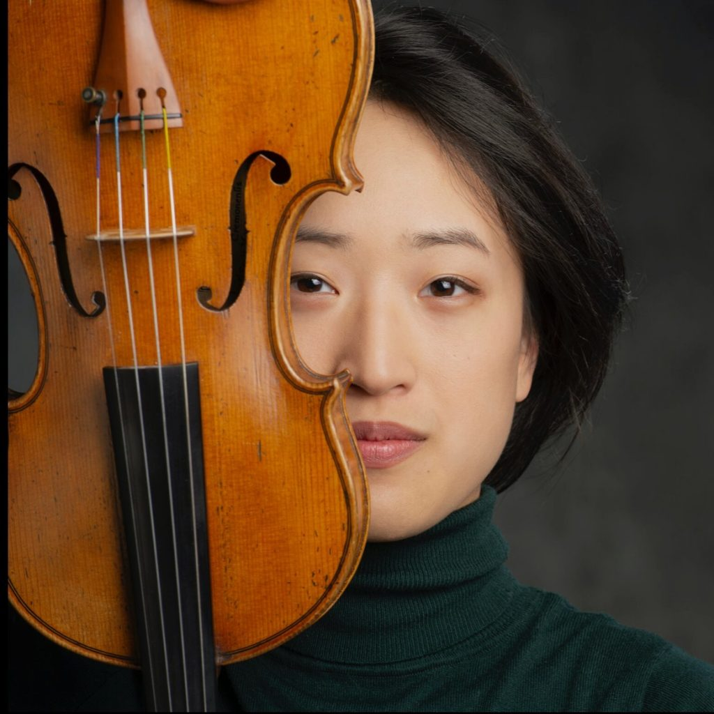 A photograph of Deanna Choi. Deanna is an Asian woman with dark brown eyes and chin-length black hair. She wears a dark green turtleneck and holds a violin upside down which covers part of the right side of her face.