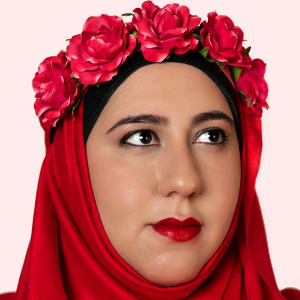 A close up of Hanan's face and head. Hanan is wearing a bright red hijab with a garland of red roses on top of her head. She is looking up to the right with dark brown eyes and she is wearing bright red lipstick.