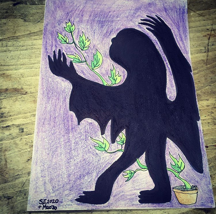 Drawing of a black-shadowy figure that is shaped like an ominous winged two-legged creature with long draping bat-like wings and a prolonged alien-resembling head. It has thick hands resembling claws. It is shaded in with bold opaque marker with clean distinct lines around the body. In the bottom right corner there is a long green pathos plant growing out of a terracotta pot. It is vine like and stretches up to the left top corner of the page. The background of the image is various crayons of magenta, and purple hues to create a textured effect of foggy light.